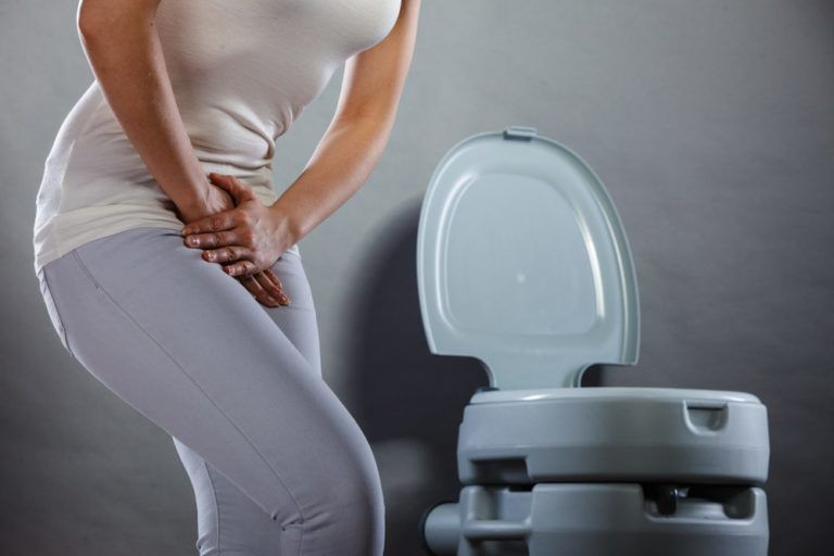 Woman suffering from Urinary Incontinence holding her lower abdomen in front of a toilet