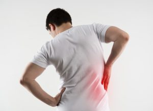 Man in discomfort holding his right side due to kidney pain